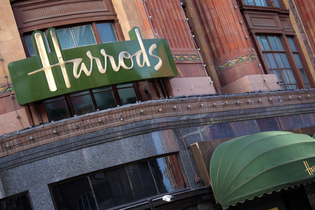 London, United Kingdom - September 23, 2011: Illuminated Harrods sign and entrance canopy on the outside wall of the famous department store in Knightsbridge London.