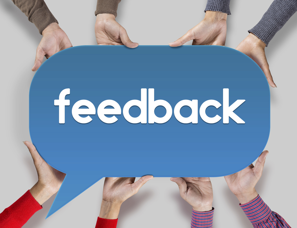 """Cropped image of group of friends hands holding a blue speech bubble with text """"Feedback"""" symbolizing customer interaction."""