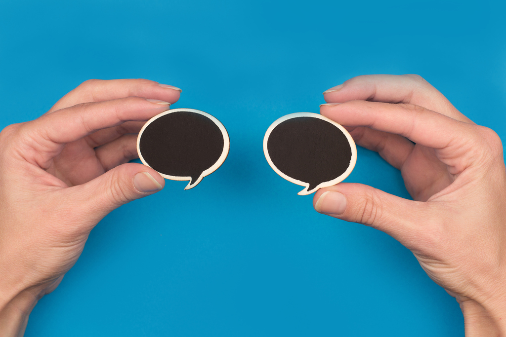 hands holding two black speech bubbles on blue background