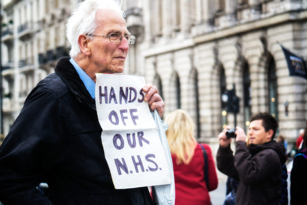 Old man with sign saying hands off our NHS