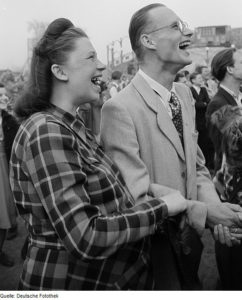 A black and white photo of two people laughing