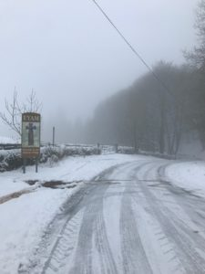 A snow covered road leading into the village of Eyam